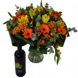 זר פרחים כתום באגרטל ויין אדום